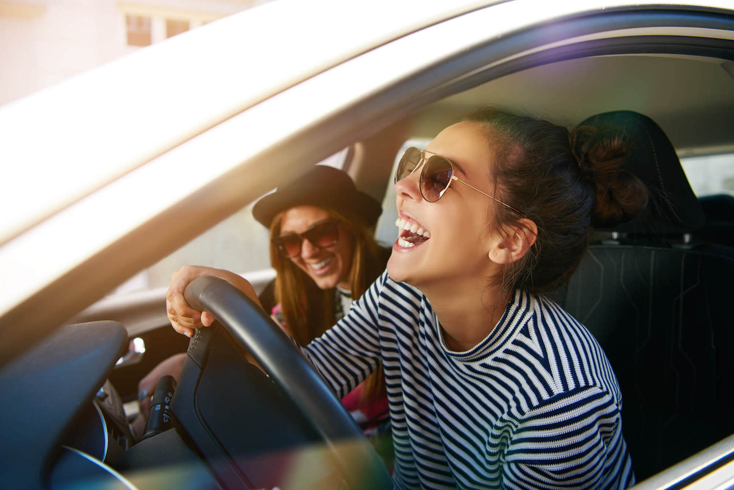 Two girls laughing in a car
